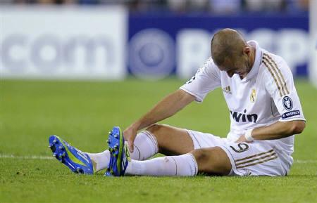 Real Madrid's Karim Benzema sits on the pitch after sustaining an injury during their Champions League Group D soccer match against Ajax Amsterdam at the Santiago Bernabeu stadium in Madrid September 27, 2011. REUTERS/Felix Ordonez