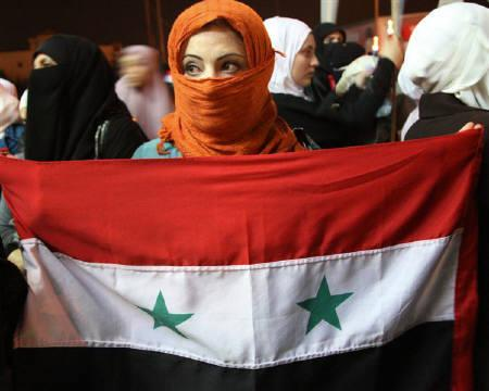 A woman holds a Syria flag as Jordanians and Syrians living in Jordan shout slogans against Syria's President Bashar Al-Assad during a protest outside the Syrian embassy in Amman October 3, 2011. REUTERS/Majed Jaber