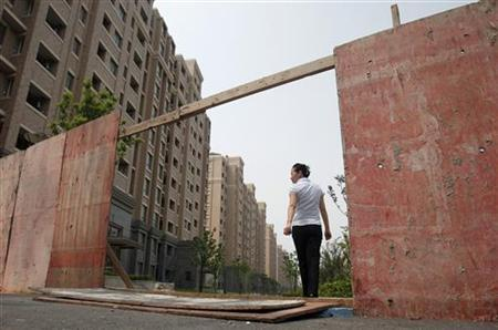 A real estate agent walks next to empty apartments at a new residential area in Shanghai September 8, 2011.   REUTERS/Carlos Barria