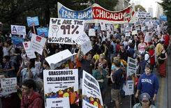 """Участники акции протеста """"Stand Up Chicago"""" проходят по одной из улиц Чикаго, 10 октября 2011 года. Тысячи демонстрантов собрались в понедельник в центре Чикаго, протестуя против экономического неравенства в духе продолжающейся с сентября акции протеста """"Захвати Уолл-Стрит"""" в Нью-Йорке. REUTERS/Frank Polich"""