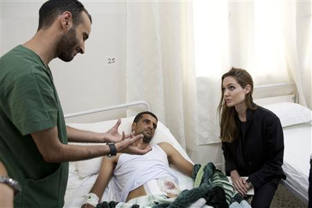 Actress and U.N. goodwill ambassador Angelina Jolie (R) visits a patient in a hospital in Misrata during her Libya visit October 11, 2011. REUTERS/Jason Tanner/Handout