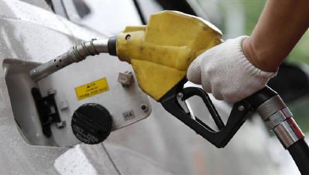 An employee of a gas station fills the tank of a car at a gas station in Seoul June 24, 2011. REUTERS/Truth Leem/Files