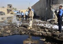 Солдат и полицейские осматривают место взрыва возле полицейского участка в Багдаде, 12 октября 2011 года. По меньшей мере 17 человек погибли и 70 получили ранения в результате двух устроенных смертниками взрывов и серии других нападений боевиков на сотрудников полиции в Багдаде, сообщили власти. REUTERS/Stringer