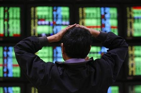 A man looks at stock market prices on computer monitors inside a securities company in Taipei December 2, 2008.   REUTERS/Nicky Loh