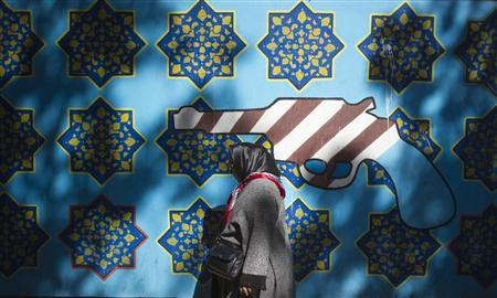 An Iranian woman walks past an anti-U.S. mural on the wall of the former U.S. embassy in Tehran, October 12, 2011. REUTERS/Morteza Nikoubazl