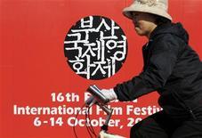 Ciclista passa em frente ao logo do Festival de Cinema de Busan, na Coreia do Sul. O festival de cinema mais renomado da Ásia terminou nesta sexta-feira na cidade portuária de Busan, na Coreia do Sul, e filmes de novos diretores do Irã e das Filipinas levaram os principais prêmios, reafirmando o foco do evento nos talentos asiáticos emergentes. 06/10/2011 REUTERS/Ben Weller