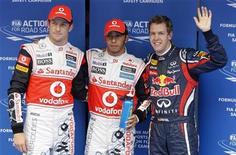 Lewis Hamilton (centro), da McLaren, seu colega de equipe Jenson Button (esq) e Sebastian Vettel, da Red Bull, após treino classificatório antes do Grande Prêmio da Coreia do Sul, em Yeongam. Hamilton foi o autor do melhor tempo no treino classificatório, acabando com a série de 16 pole positions consecutivas para a equipe Red Bull. 15/10/2011  REUTERS/Lee Jae-won