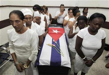 The Ladies in White, a group made up of family members of imprisoned dissidents, stand around the coffin of Laura Pollan at a funeral home in Havana October 14, 2011. REUTERS/Enrique de la Osa
