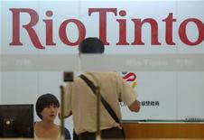 Сотрудница Rio Tinto Limited общается с клиентом в офисе компании в Шанхае, 5 августа 2010 года. Горнорудный гигант Rio Tinto в понедельник выставил на продажу алюминиевые активы на $8 миллиардов по всему миру, хотя лишь четыре года назад купил алюминиевую корпорацию Alcan за $38 миллиардов.  REUTERS/Stringer