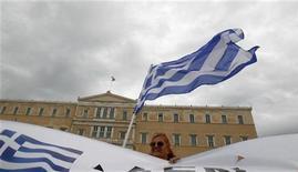 Демонстрантка размахивает греческим флагом во время акции протеста в Афинах, 15 октября 2011 года. Грецию на этой неделе ждет суровая проверка: значительная часть страны, как ожидается, замрет в 48-часовой забастовке, кульминация которой намечена на четверг, когда парламент будет голосовать по вопросу о мерах жесткой экономии, требуемых международными кредиторами. REUTERS/Yiorgos karahalis
