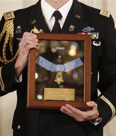 A member of the White House honor guard holds a Medal of Honor during a ceremony at the White House in Washington March 3, 2008.  REUTERS/Jason Reed