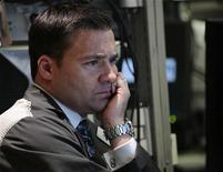 Трейдер на торгах Нью-Йоркской фондовой биржи 17 октября 2011 года. Фондовые индексы США мало изменились в начале торгов на фоне угроз Moody's понизить прогноз кредитного рейтинга Франции и не впечатливших рынки отчетов ряда крупных корпораций.   REUTERS/Brendan McDermid