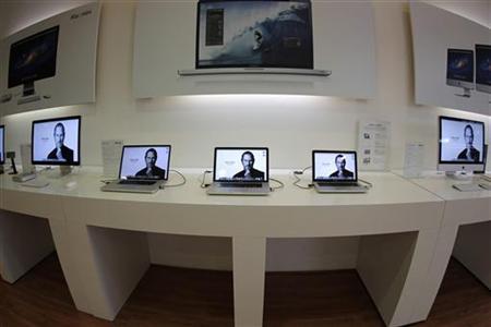 Apple computers display pictures of Steve Jobs on screen in the iShop in Guatemala City, October 6, 2011.  REUTERS/Jorge Dan Lopez