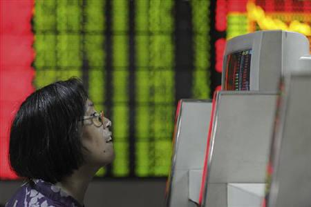 An investor looks at a computer screens showing stock information at a brokerage house in Hefei, Anhui province October 10, 2011. REUTERS/Stringer