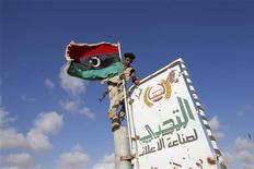 An anti-Gaddafi fighter puts up a rebel flag September 8, 2011.  REUTERS/Youssef Boudlal