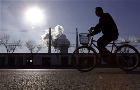 A chimney billows smoke from a coal-burning power station behind a workman riding a bicycle in Beijing December 14, 2010. REUTERS/David Gray/Files
