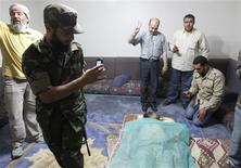 <p>Men take pictures of Muammar Gaddafi's corpse displayed at a house in Misrata, October 20, 2011. REUTERS/Thaier al-Sudani</p>