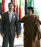 Ливийский лидер Муаммар Каддафи приветствует сирийского президента Башара Асада на открытии 23-го саммита Лиги арабских государств в Сирте 27 марта 2010. Новость об убийстве Каддафи вызвала новую волну демонстраций в Сирии с требованием отставки Асада. REUTERS/Ismail Zitouny