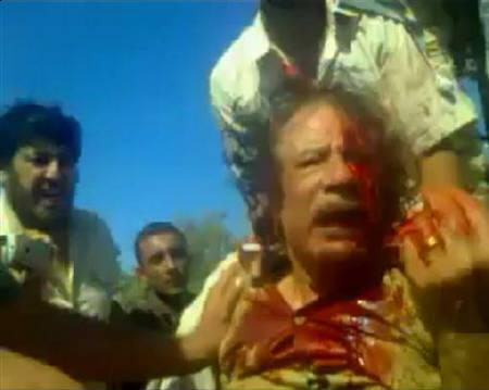 This still image taken from amateur video posted on a social media website and obtained by Reuters, October 21, 2011, shows former Libyan leader Muammar Gaddafi, covered in blood, after his capture by NTC fighters in Sirte. REUTERS/Social Media Website via Reuters TV