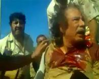 This still image taken from amateur video posted on a social media website and obtained by Reuters, October 21, 2011, shows former Libyan leader Muammar Gaddafi, covered in blood, after his capture by NTC fighters in Sirte. Gaddafi will be buried according to Muslim rites within 24 hours, a Libyan transitional government force commander said on Friday, and witnesses said the body bore a visible bullet hole in the head. Gaddafi was captured alive in his hometown of Sirte on Thursday but died later while in the hands of fighters in circumstances that are still not clear.  REUTERS/Social Media Website via Reuters TV (LIBYA - Tags: POLITICS CIVIL UNREST) FOR EDITORIAL USE ONLY. NOT FOR SALE FOR MARKETING OR ADVERTISING CAMPAIGNS. THIS IMAGE HAS BEEN SUPPLIED BY A THIRD PARTY. IT IS DISTRIBUTED, EXACTLY AS RECEIVED BY REUTERS, AS A SERVICE TO CLIENTS