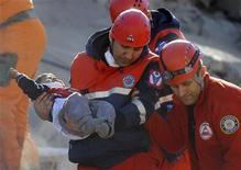 Спасатели извлекли мальчника из-под обломков здания в Эрджише 24 октября 2011. Турецкие власти подтвердили в понедельник гибель более 200 человек в результате сильного землетрясения на юге-востоке. Поиски под завалами продолжаются, и число жертв может оказаться выше. REUTERS/Stringer/Turkey