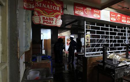 Policemen inspect the scene of an explosion inside a pub in Kenya's capital Nairobi, October 24, 2011. REUTERS/Thomas Mukoya