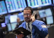 Трейдер следит за торгами на бирже в Нью-Йорке, 24 октября 2011 года. Американские акции выросли в понедельник, так как множество новостей в сфере слияний и поглощений и хорошие результаты Caterpillar поддержали настроения инвесторов. REUTERS/Brendan McDermid