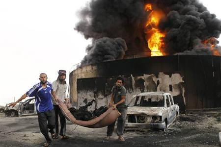 ATTENTION EDITORS - VISUALS COVERAGE OF SCENES OF DEATH AND INJURYResidents carry a dead body that was found near the site of burning tankers, after an  unidentified explosion, on the outskirts of Sirte October 24, 2011. REUTERS/Youssef Boudlal