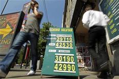 Люди проходят мимо обменного пункта в Бухаресте, 19 августа 2011 года. Евро торгуется ниже уровня закрытия торгов вторника, растеряв часть набранных позиций, и может пойти еще ниже в случае невнятных итогов саммита лидеров еврозоны. REUTERS/Bogdan Cristel
