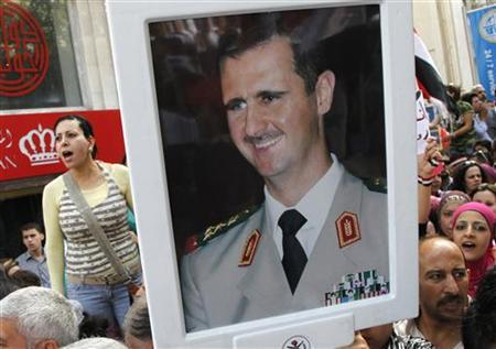 Supporters of Syrian President Bashar al-Assad's hold pictures of al-Assad during a rally at al-Sabaa Bahrat square in Damascus October 12, 2011.   REUTERS/ Khaled al-Hariri