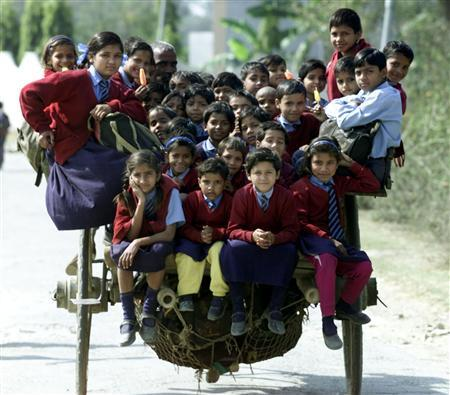 Indian children ride in a cart on the way home from school in the outskirts of New Delhi in this file picture taken, February 26, 2001.     REUTERS/Pawel Kopcznski/Files