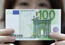 Работница банка в Тайбее держит купюру в 100 евро, 10 мая 2010 года. Евро растет более чем на 1 процент и продолжает торговаться около максимума семи недель, достигнутого в четверг, благодаря появлению долгожданного плана борьбы с долговым кризисом еврозоны, согласованного европейскими лидерами минувшей ночью. REUTERS/Pichi Chuang