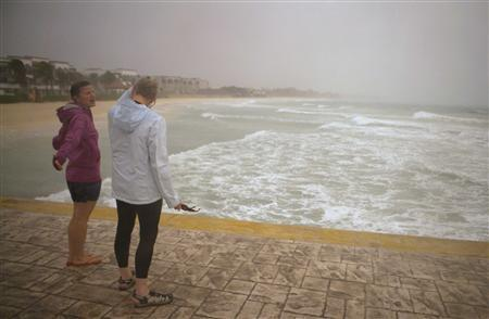 Tourists stand in the rain brought by Hurricane Rina in Playa del Carmen October 27, 2011. REUTERS/Victor Ruiz Garcia