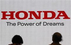 Посетители выставочного зала Honda Motor в Токио стоят перед логотипом компании, 31 октября 2011 года. Honda Motor Co отказалась от годового прогноза прибыли в понедельник из-за неопределенности в состоянии мировой экономики и валютного рынка на фоне резкого падения прибыли за квартал. REUTERS/Issei Kato