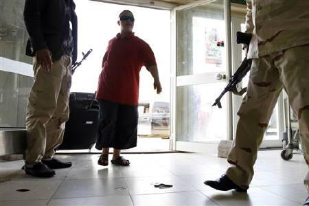 A passenger drags his suitcase as he walks past National Transitional Council (NTC) fighters as they secure the main entrance of Tripoli's Mitiga airport, October 30, 2011. REUTERS/ Jamal Saidi