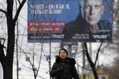 Женщина проходит мимо рекламного баннера в Москве, 25 ноября 2010 года. Российский рынок рекламы притормозил рост в третьем квартале по сравнению с первой половиной 2011 года из-за сокращения ее объема в традиционных сегментах, и лишь интернет показывает стабильный годовой подъем.   REUTERS/Denis Sinyakov