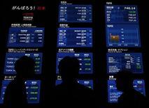 Посетители фондовой биржи в Токио смотрят на элеткронные табло, 2 ноября 2011 г. Фондовые площадки Китая и Гонконга выросли по итогам среды после оптимистичных заявлений замминистра финансов КНР, но рынки акций в Японии и Корее продолжили падение из-за греческого референдума. REUTERS/Yuriko Nakao