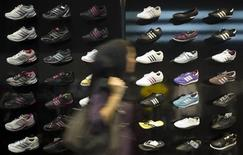 Женщина проходит мимо витрины магазина Adidas в Тегеране, 24 октября 2010 года. Немецкий Adidas вновь повысил прогноз продаж на 2011 год благодаря сильному спросу на спортивные товары на развивающихся рынках, а также увеличению площадей фирменных магазинов компании. REUTERS/Morteza Nikoubazl