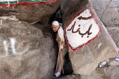 <p>A Muslim pilgrim crouches as he makes his way down Mount Al-Noor during the annual haj pilgrimage in Mecca, November 2, 2011. REUTERS/Ammar Awad</p>