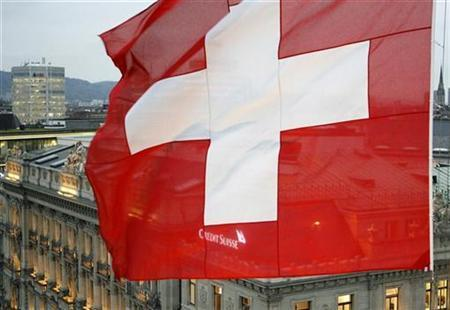 A Swiss national flag waves in front of the headquarters of Swiss bank Credit Suisse at the Paradeplatz square in Zurich October 23, 2008.   REUTERS/Arnd Wiegmann (SWITZERLAND)