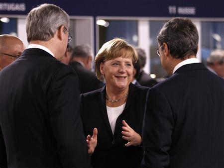 Germany's Chancellor Angela Merkel (C) talks with Canada's Prime Minister Stephen Harper (L) and new European Central Bank (ECB) President Mario Draghi (R) before a meeting on the second day of the G20 Summit in Cannes November 4, 2011. REUTERS/Kevin Lamarque (FRANCE - Tags: POLITICS BUSINESS)