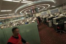 Трейдер (слева) проходит по торговому залу биржи в Гонконге, 23 ноября 2010 года. Фондовые рынки Азии закрылись во вторник снижением из-за сильного роста стоимости заимствования для Италии, который может усугубить долговой кризис еврозоны, и в ожидании данных об инфляции в Китае. REUTERS/Tyrone Siu