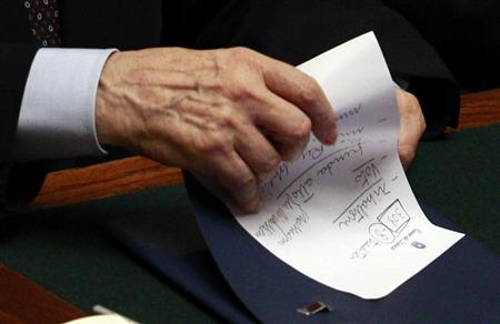 Italian Prime Minister Silvio Berlusconi holds a memo reading ''308 (the result of the vote) - 8 traitors - political reversal - vote - take note: resign - Republic President - a solution'' during a finances vote at the parliament November 8, 2011.  REUTERS/Tony Gentile