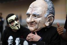 """Демонстрант в маске смотрит на голову куклы, изображающей медиамагната Руперта Мердока на ежегодном собрании акционеров News Corp. в Лос-Анджелесе 21 октября 2011.  Принадлежащий компании медиамагната Руперта Мёрдока News Corp британский таблоид News of the World, закрытый в июле после скандала с прослушиванием телефонов, шпионил за принцем Уильямом, а также другими известными людьми, сообщила """"Би-би-си"""" во вторник. REUTERS/David McNew"""