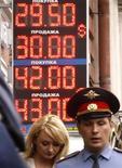 Пешеходы проходят мимо электронного табло обменного пункта в Санкт-Петербурге, 9 августа 2011 года. Рубль подешевел к бивалютной корзине и её компонентам в начале торгов четверга из-за напряженной ситуации на глобальных рынках, связанной с углублением европейского долгового кризиса и спровоцировавшей бегство инвесторов из рискованных активов. REUTERS/Alexander Demianchuk