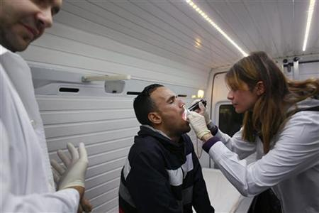 Nurse Maria Vatista examines an immigrant inside a mobile HIV testing van in Omonia square in Athens October 31, 2011. REUTERS/Yannis Behrakis