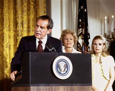 FILE PHOTO 9AUG74 - U.S. President Richard Nixon (L), listened to by First lady Pat Nixon and daughter Tricia Nixon (R), says goodbye to family and staff in the White House East Room on August 9, 1974.