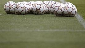 Футбольные мячи лежат на поле в Мадриде, 21 мая 2010 года. Матчи плей-офф отборочного цикла чемпионата Европы 2012 года, а также товарищеские игры сборных команд пройдут в выходные. REUTERS/Kai Pfaffenbach