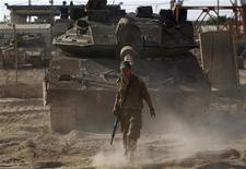 Израильский солдат на фоне танка на границе с Сектором Газа 20 августа 2011 года. Израильские войска с Западного берега река Иордан по ошибке застрелили местного раввина, приняв его за палестинского боевика, сообщили армейские источники и местные жители в пятницу. REUTERS/Baz Ratner