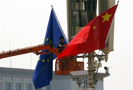 A worker on a cherry picker hangs a European Union flag next to a Chinese national flag at Beijing's Tiananmen Square in Beijing May 16, 2011 ahead of a visit by President of the European Council,  Herman van Rompuy. REUTERS/David Gray